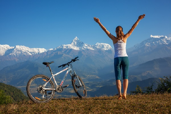 happy lady at top of hill with bike