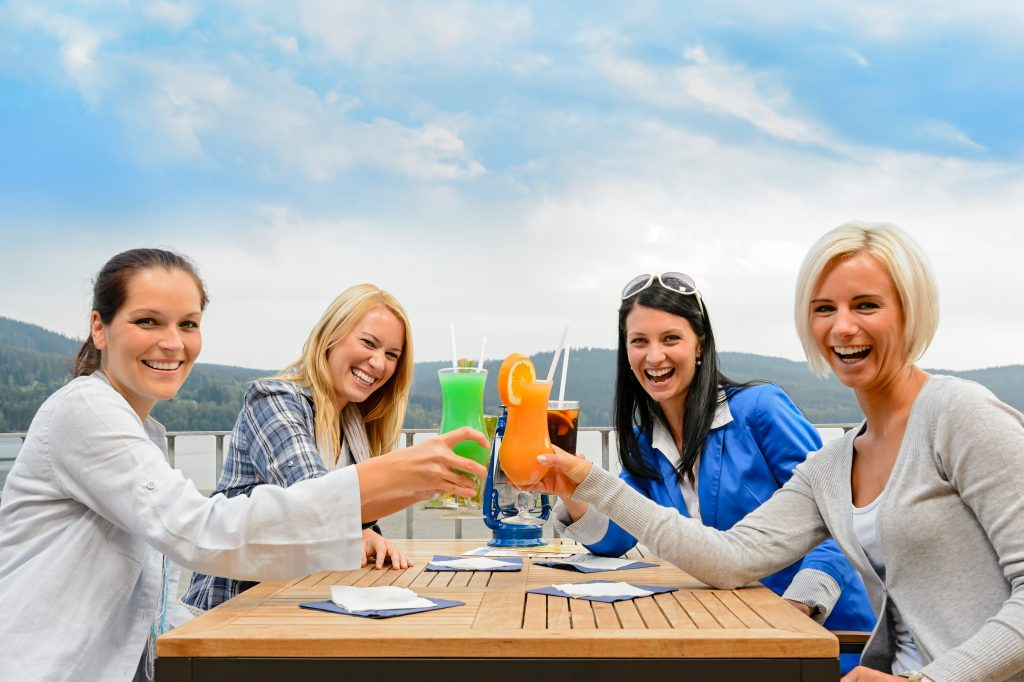 Cheerful women toasting with cocktails at outdoor restaurant summer terrace
